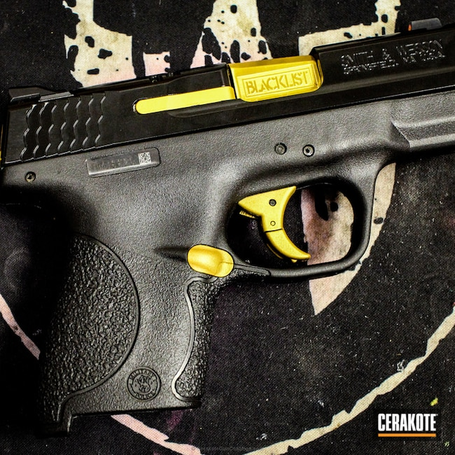 M&P Shield done in Gold and Mad Black Elite