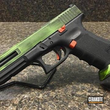 Cerakoted Zev Glock In A Green / Black Battleworn Finish With Orange Accents