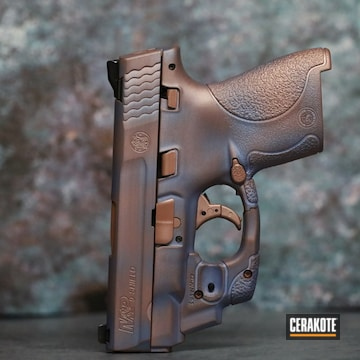 Distressed Smith & Wesson M&p Shield Pistol Cerakoted Using Rose Gold And Polar Blue