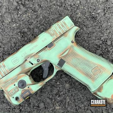 Distressed Glock 43x Cerakoted Using Midnight Bronze, Zombie Green And Sky Blue