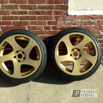 A Pair Of Automotive Wheels With Spanish Gold And Clear Vision