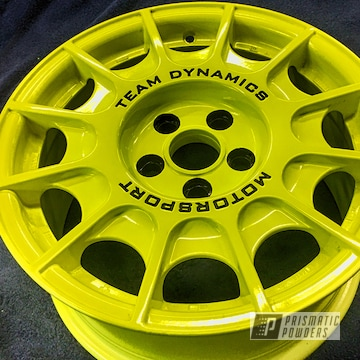 A Classic Rally Wheel By Team Dynamic Motorsport In A Neon Yellow With Black Letters And Lug Holes